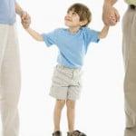 child standing between parents