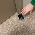 Photo of hand picking up wallet from floor