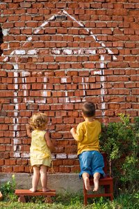 children drawing with chalk on a brick wall