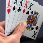 hand holding playing cards: 3 Kings and 2 Aces
