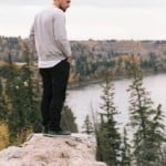 Man standing on cliff looking down at trees