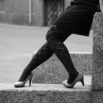 body of a woman in heels leaning on a wall