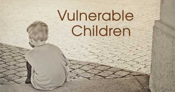 cover banner: Vulnerable Children: small boy sitting alone on a step viewed from the back