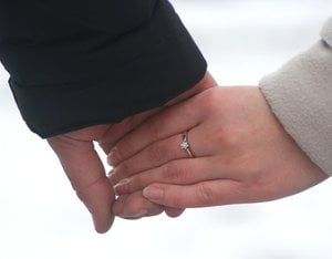 holding hands with engagement ring